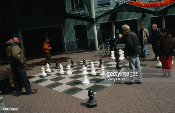 Working out their brain cells at an outdoor oversized chess game on max Euweplein.