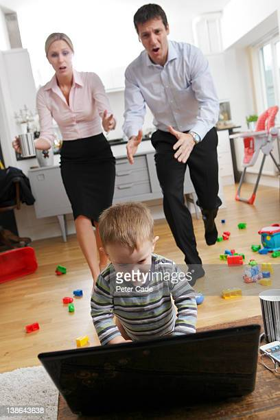 working parents rushing to stop child on laptop