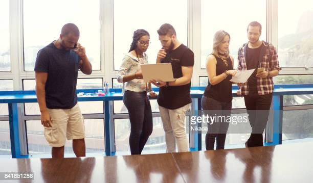 working people standing against glass window in creative office
