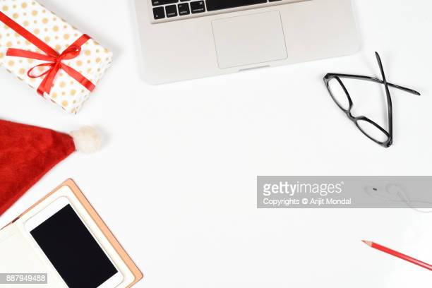 working place on christmas season, christmas gift on white table with laptop and smartphone, top view flat lay - christmas banner stock photos and pictures