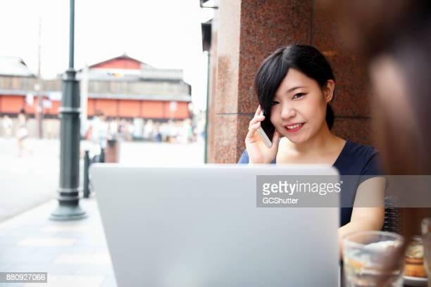 カフェでノート パソコンやスマート フォンを使用してリモートで作業