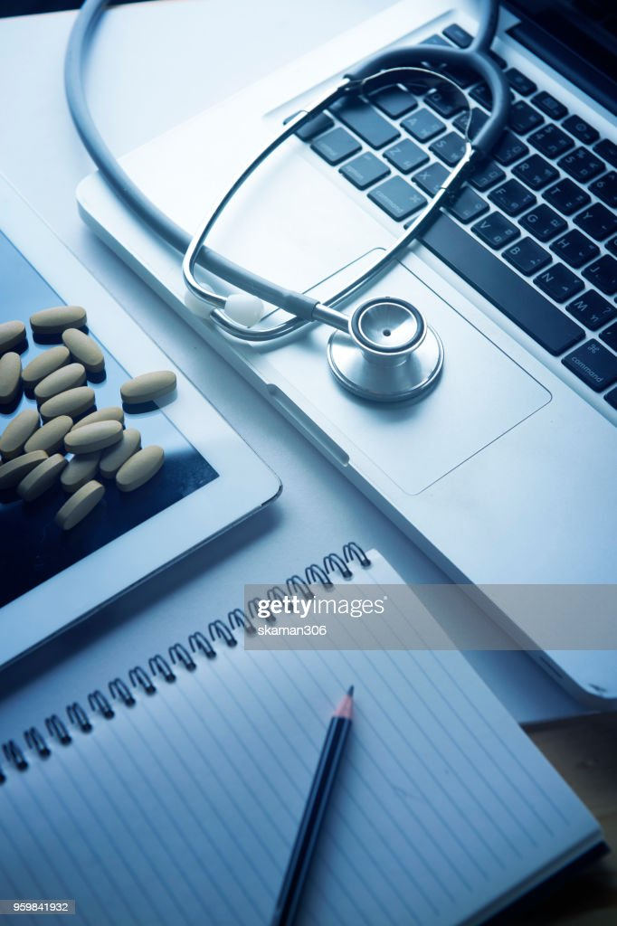 working space of Doctor with stethoscope with medicine tablet and notebook for consult patient : Stock-Foto