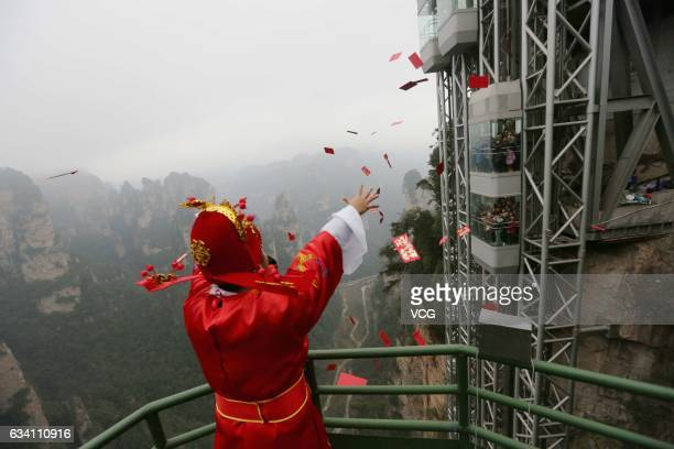 Working staff dressed as the god of wealth drops red envelops at the top of Bailong Elevator of Wulingyuan scenic area on February 6 2017 in...