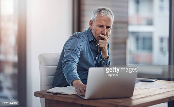 working through ways to better manage his business - man in office stock photos and pictures