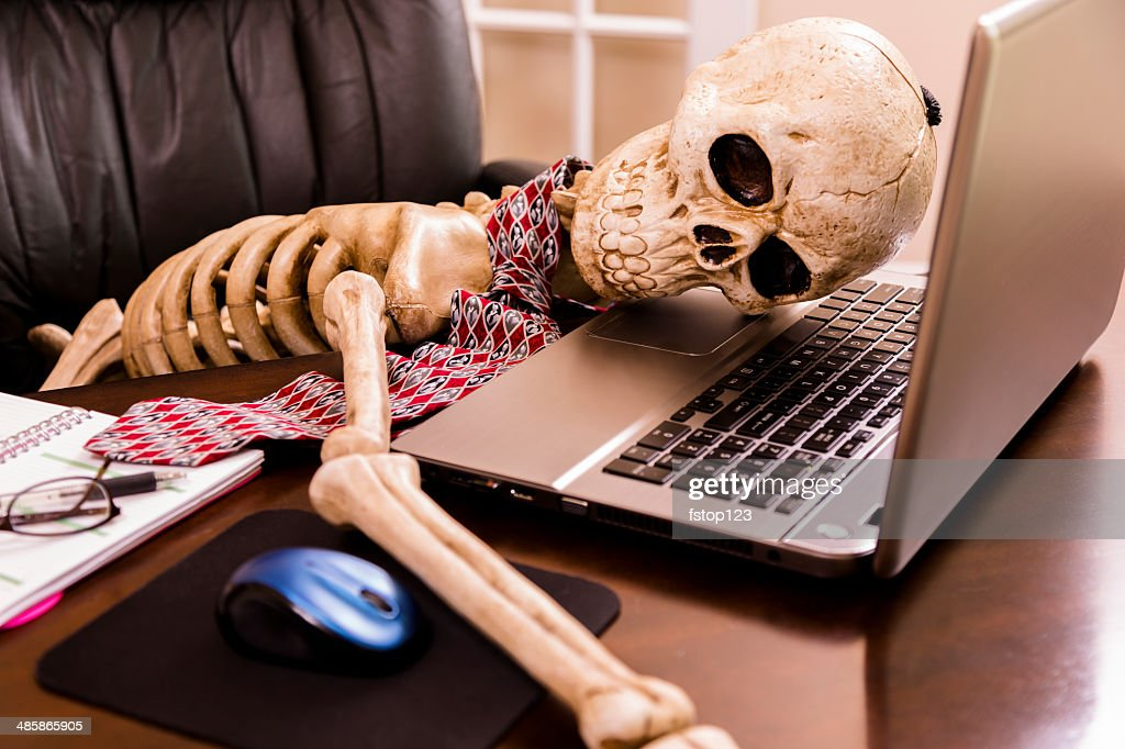 Working to death.  Business man's skeleton using laptop in office. : Stockfoto