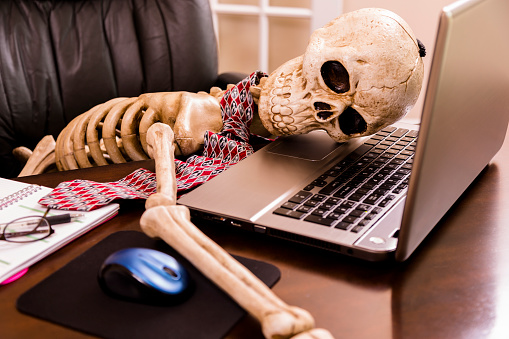 Working to death.  Business man's skeleton using laptop in office. 485865905