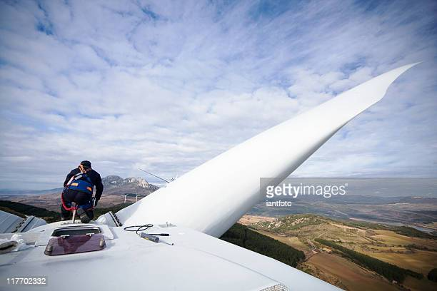 working upon wind turbine - windmills stock photos and pictures