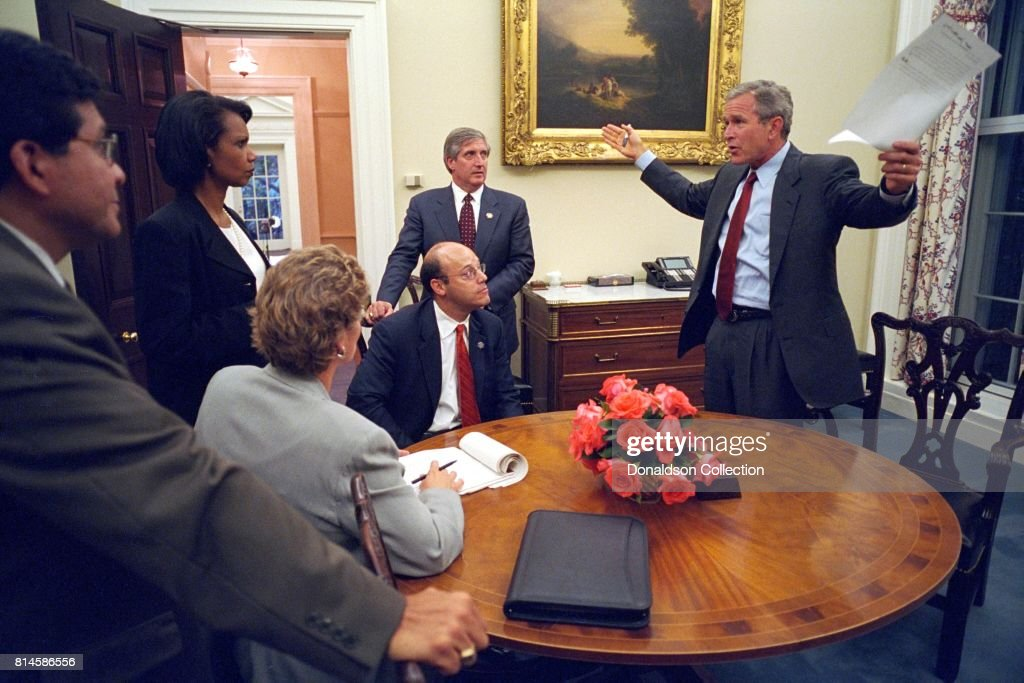 Working with his senior staff, President George W. Bush reviews the speech that he will deliver to the nation the evening of Tuesday, Sept. 11, 2001, from the Oval Office. Pictured from left are: Alberto Gonzales, White House Counsel; Condoleezza Rice, National Security Adviser; Karen Hughes, Counselor; Ari Fleischer, Press Secretary, and Andy Card, Chief of Staff. Photo by Paul Morse, Courtesy of the George W. Bush Presidential Library/Getty Images