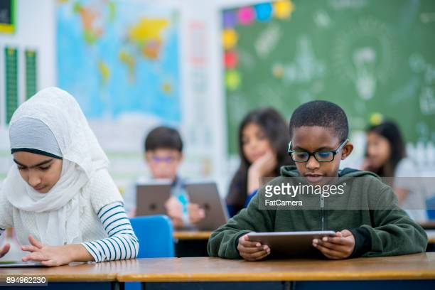working with tablet computers - migrant children stock photos and pictures
