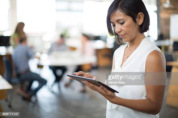 working with technology in modern office - leanincollection working women stock photos and pictures
