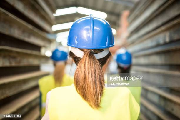 working women in concrete factory. cordoba, working women with helmets go to work in factory. women power - international womens day stock pictures, royalty-free photos & images