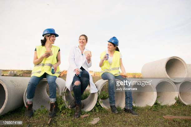 working women take the snack outside a company building cement structures. - international womens day stock pictures, royalty-free photos & images
