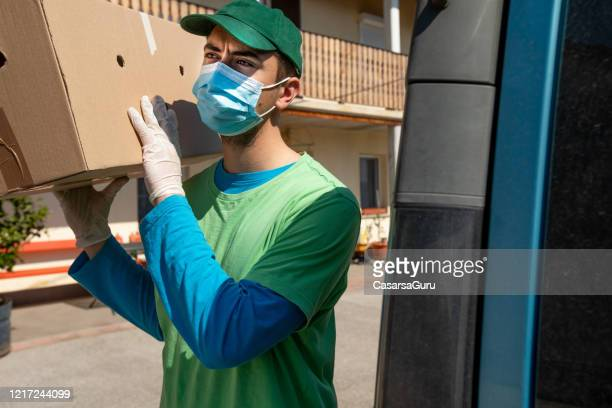 working young adult home delivery man during coronavirus pandemic - stock photo - essential services stock pictures, royalty-free photos & images