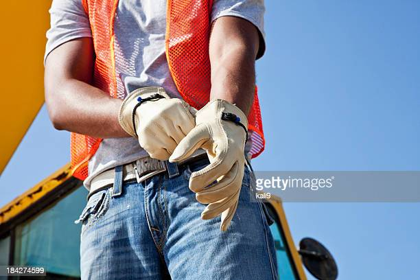 workman at construction site putting on gloves - work glove stock photos and pictures