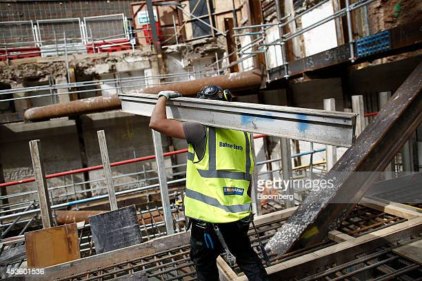 A workman carries a metal girder during excavation and building works at Balfour Beatty Plc's St James's Market construction site a joint Crown...