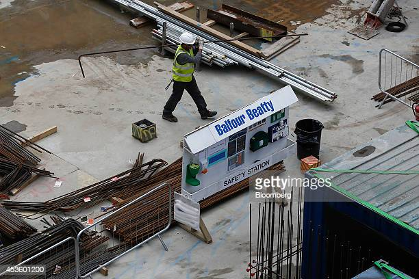 A workman carries a metal reinforcement rod past a safety station during building works at Balfour Beatty Plc's St James's Market construction site a...