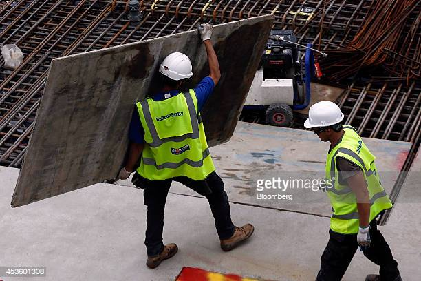 A workman carries a protective floor board during building works at Balfour Beatty Plc's St James's Market construction site a joint Crown Estate and...