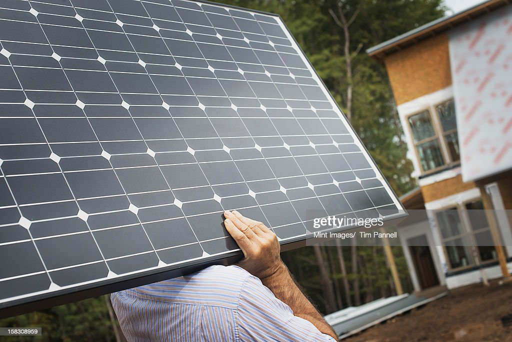 A workman carrying a large solar panel at a green house construction site. : Stock Photo