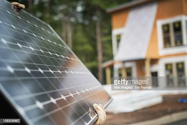 Un travailleur transportant un grand panneau solaire sur un green house construc