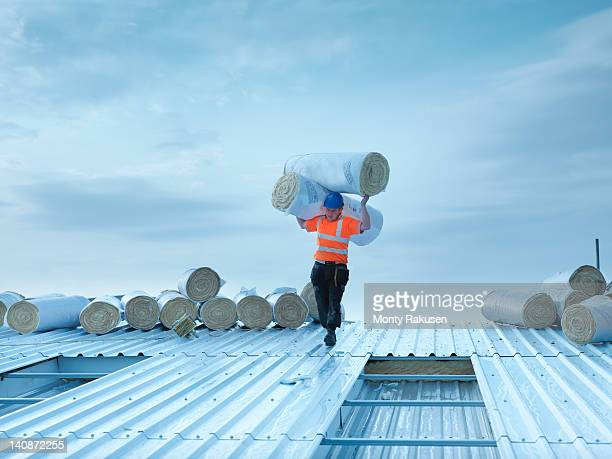 Workman carrying rolls of insulation to install into factory roof