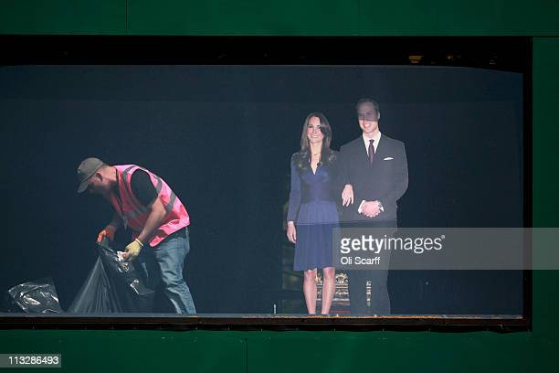 Workman cleans a temporary television studio with a cardboard cut-out of Prince William, Duke of Cambridge and Catherine, Duchess of Cambridge in...