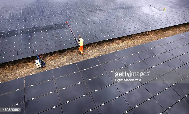 Workman cleans panels at Landmead solar farm on July 29, 2015 near Abingdon, England. The 46 megawatt capacity installation was the largest in the...