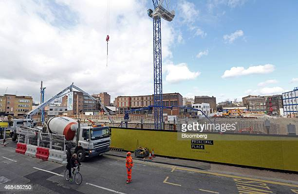 Workman controls traffic flow outside the construction site of Principal Place, a joint development by Brookfield Property Partners LP, Concord...