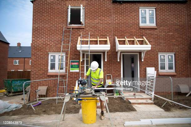 Workman cuts lengths of skirting board at a construction site, operated by Persimmon Plc, in Towcester, U.K., on Wednesday, Sept. 16, 2020. Surging...