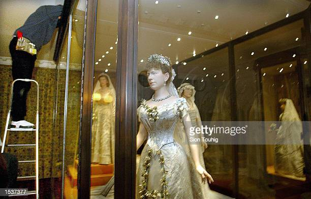 A workman finishes off a display case holding a mannequin of Britain's Queen Mary wearing her wedding dress in front of models of Queen Elizabeth and...
