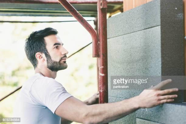 workman, einbau von wärmedämmung an einer innenwand - isoliert stock-fotos und bilder
