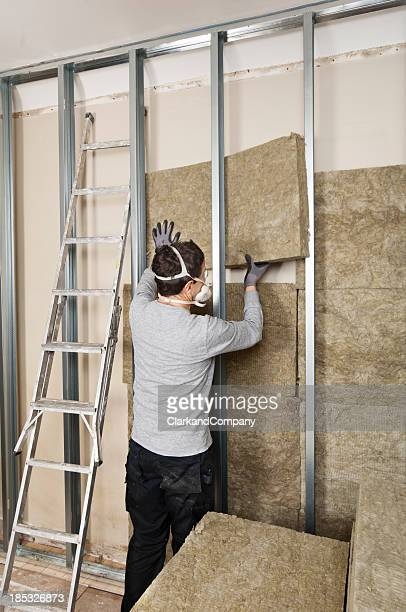 Workman Fitting Wall Insulation to an Existing Wall