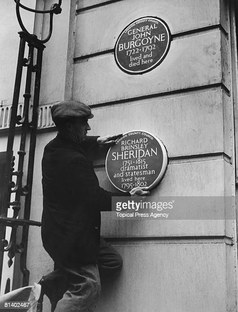 A workman fixes a second plaque to the wall of 10 Hertford Street Westminster 11th November 1954 The first commemorates the residence at that address...
