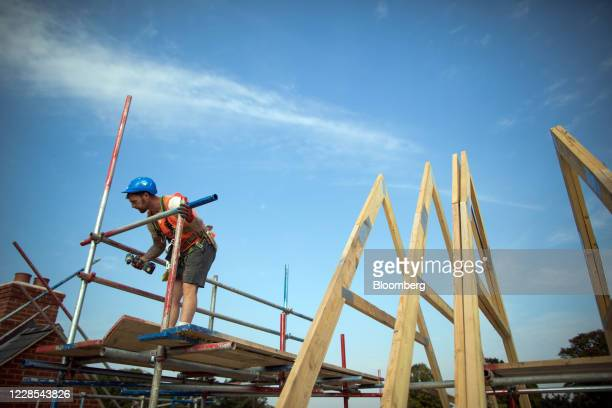 Workman fixes scaffolding into place on a Charles Church house at a residential construction site, operated by Persimmon Plc, in Towcester, U.K., on...