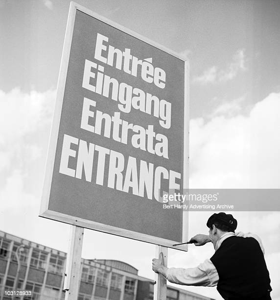A workman fixes up an entrance sign written in four languages French German Italian and English 6th September 1962