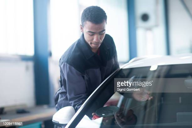 workman fixing car windshield in workshop - sigrid gombert stock pictures, royalty-free photos & images