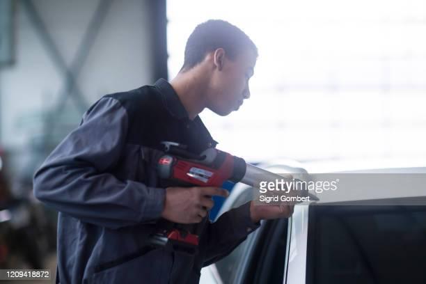 workman fixing car windshield in workshop - sigrid gombert fotografías e imágenes de stock
