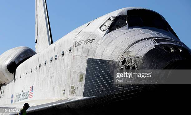 A workman helps in the process of prepping the Space Shuttle Endeavour to move the final few yards into a temporary hangar at the California Science...