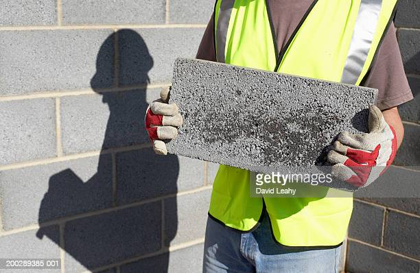 Workman holding breeze block, mid section.