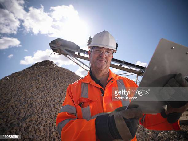 Workman holding clipboard in front of pile of crushed stones in quarry