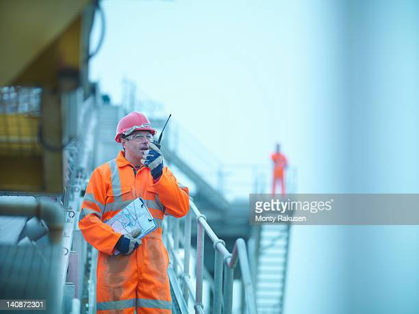 Workman in reflective clothing using walkie talkie to communicate to colleague at quarry