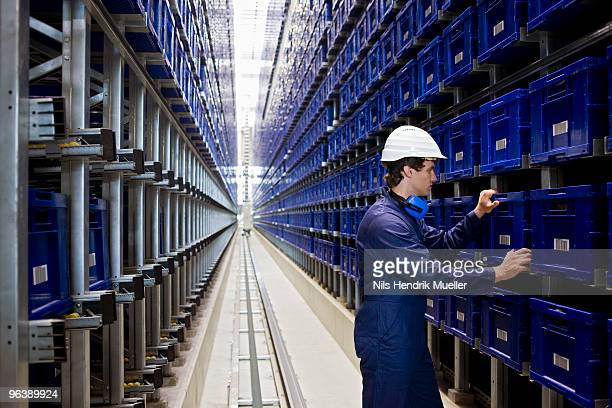 workman in storage - industrial storage bins stock pictures, royalty-free photos & images