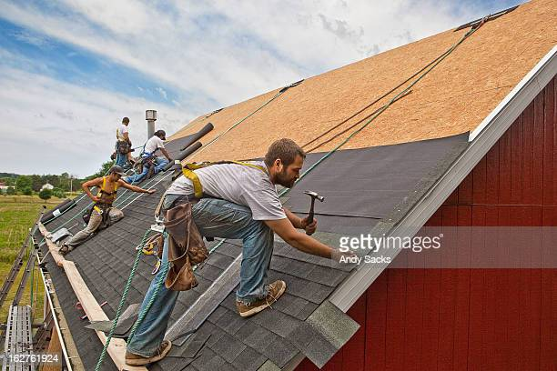workman install roof on rural building - roof stock pictures, royalty-free photos & images