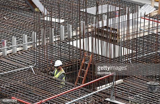 A workman installs metal reinforcement rods to support concrete during building works at Balfour Beatty Plc's St James's Market construction site a...