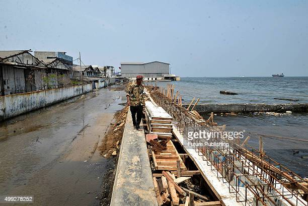 A workman iron binding on a seawall being rebuilt behind an abandoned mosque which has been surrounded by the encroaching sea in the Maura Baru...