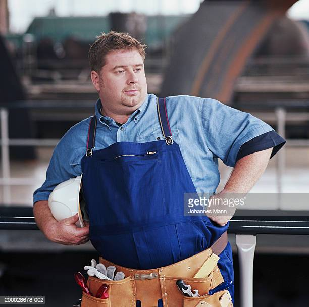 workman leaning on barrier in power station, arms akimbo - chubby photos et images de collection