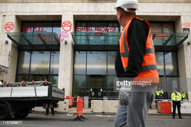 A workman looks at graffiti drawn by members and supporters of climate change activist group Extinction Rebellion on the offices of oil company Shell...