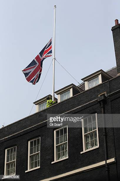 A workman lowers the Union Flag flying above Downing Street to halfmast at the news of the death of former British prime Minster Baroness Thatcher on...