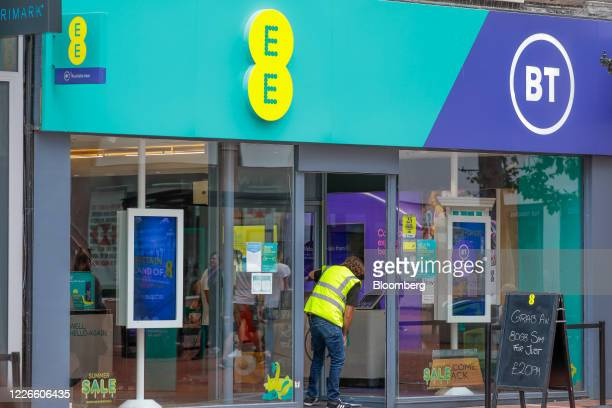 Workman measures the door of an EE mobile phone store, operated by BT Group Plc, in Reading, U.K., on Monday, July 13, 2020. U.K. Prime Minister...