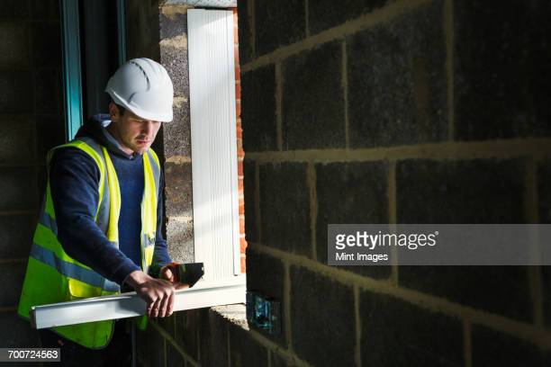 a workman on a construction site, builder in hard hat using a saw on a plank of wood. - installing stock pictures, royalty-free photos & images