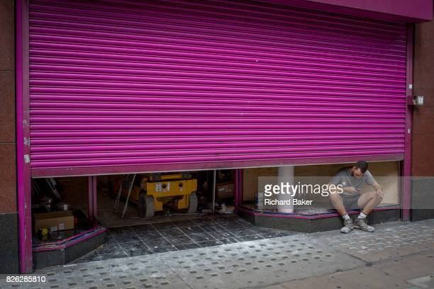 A workman on his cigarette break crouches beneath a halflowered purple shutter on 31st July 2017 in Oxford Street London England